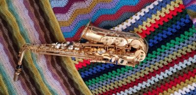 A saxophone placed on colourful woven blankets