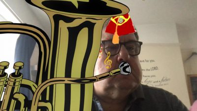 Rob demonstrating use of comical video filters, a tuba and fez hat have been added